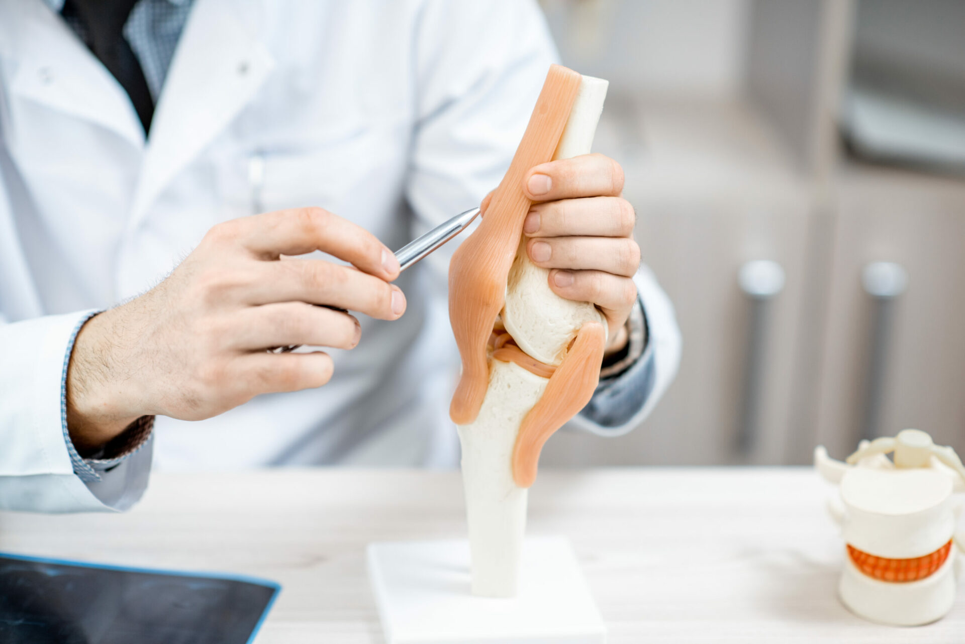 Close-up of the therapist showing knee joint model during the medical consultation